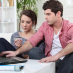 male and female couple, seated holding credit card while using laptop - credit card consolidation loans